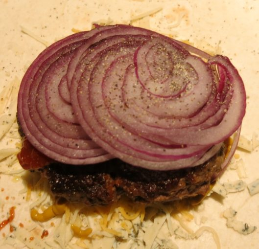 Thinly Sliced Raw Red Onion on a Burger